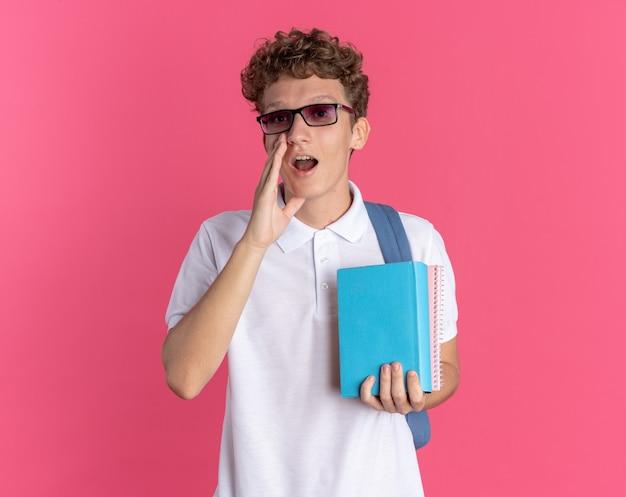 Student man in vrijetijdskleding met een bril met rugzak met notitieboekjes die schreeuwen