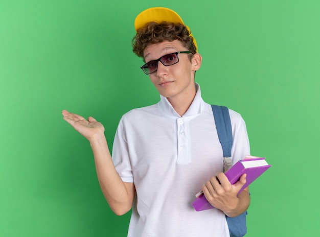 Student man in wit overhemd en gele pet met bril met rugzak met notebooks kijken naar camera verward schouderophalend schouders over groene achtergrond
