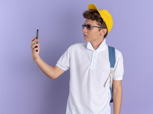 Student man in wit poloshirt en gele pet met bril met rugzak doet selfie met smartphone en ziet er zelfverzekerd uit over een blauwe achtergrond