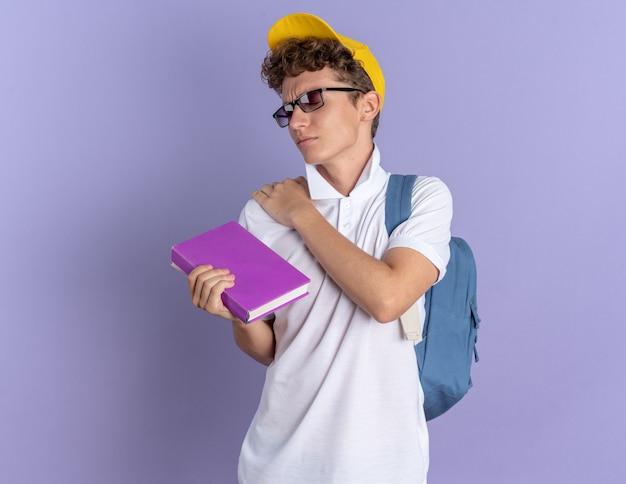 Student man in wit poloshirt en gele pet met bril met rugzak met notitieboekje die zijn schouder aanraakt en pijn voelt