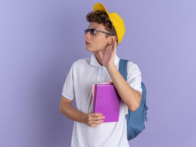 Student man in wit poloshirt en gele pet met bril met rugzak met notitieboekjes opzij kijkend geïntrigeerd met hand over oor proberend te luisteren over blauwe achtergrond