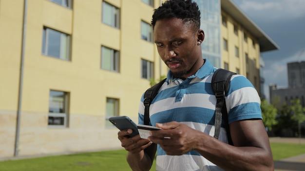 Student man kopen en betalen op internet op mobiele telefoon afro-amerikaanse man die op straat staat en online winkelt met creditcard op smartphone