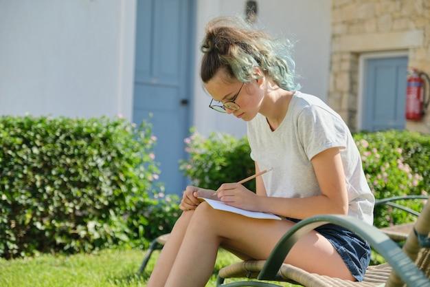 Student meisje 15, 16 jaar oud zitten buiten, schrijven in notitieblok voor leerling
