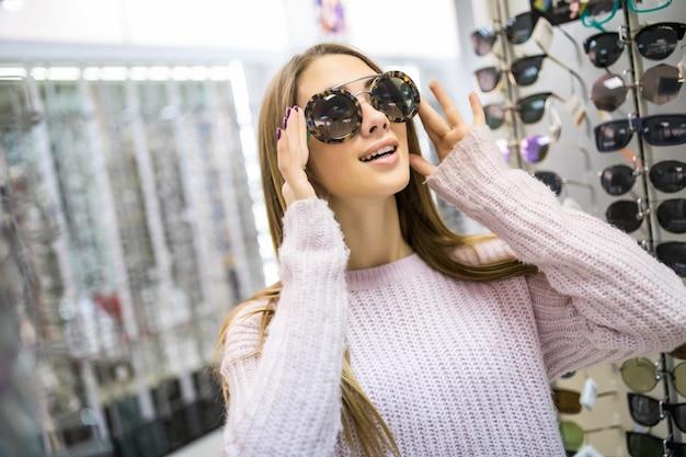 Student meisje bereidt zich voor op studie en probeert een nieuwe bril voor haar perfecte look in de professionele winkel