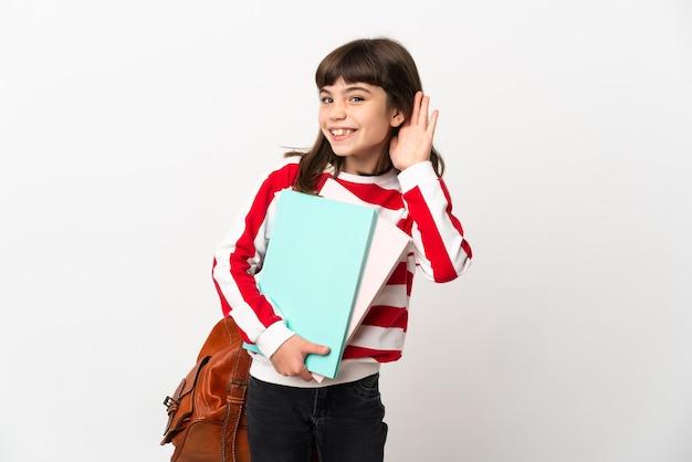 Student meisje geïsoleerd op een witte achtergrond luisteren naar iets door hand op het oor te leggen