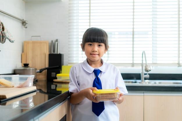 Student meisje in uniform sandwich maken voor lunchdoos in ochtendschool