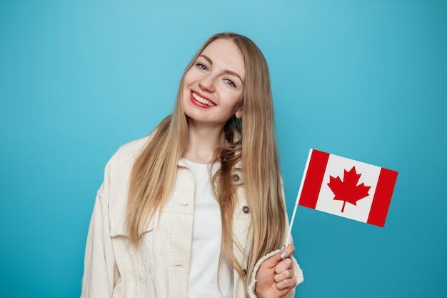 Student meisje lachend met een kleine vlag van canada en op zoek naar camera