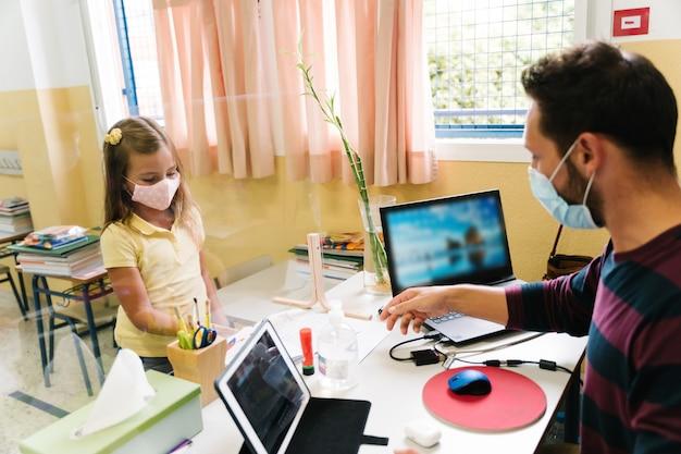 Student meisje met een masker huiswerk overhandigen aan de leraar via een methacrylaat scherm tijdens de covid pandemie. terug naar school met behoud van sociale afstand