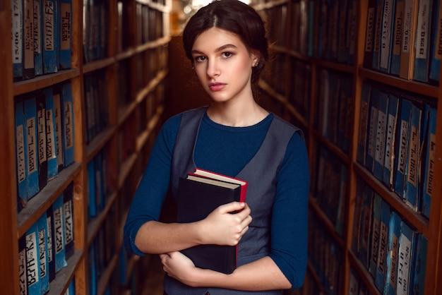 Student meisje of vrouw met boeken in bibliotheek.