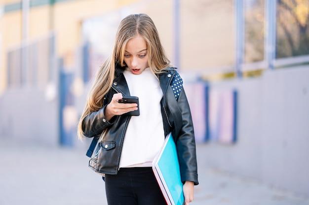 Student meisje op weg naar school met behulp van een smartphone