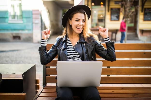 Student meisje zakenvrouw zitten op houten bankje in de stad in het park in de herfst