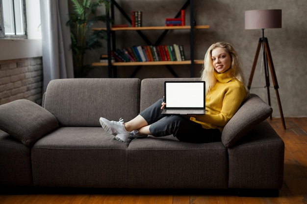 Student meisje zit op de bank met laptop kijken naar mock-up scherm, online leren op pc, e learning. close-up uitzicht