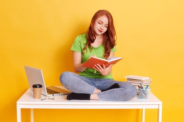 Student meisje zittend op een bureau met gekruiste benen en boek lezen
