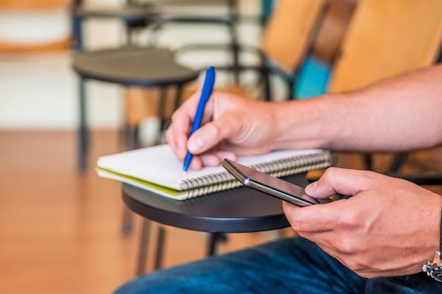 Student met behulp van een smartphone tijdens het studeren / student met martphone verslaving concept. technologie concept - student op zoek naar telefoon en iets schrijven