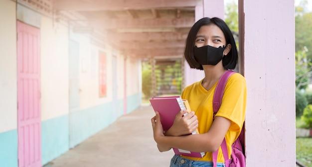 Student met gezichtsmasker op school draagt een geel overhemd