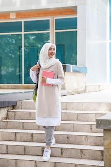 Student met hoofddoek die op campus loopt