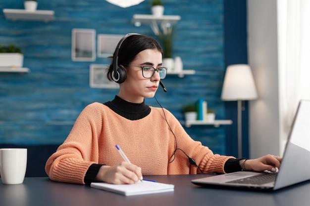 Student met koptelefoon schrijven van notities op notebook tijdens het zoeken naar communicatie-informatie met behulp van laptopcomputer. geconcentreerde tiener die huiswerk maakt terwijl hij aan het bureau in de woonkamer zit