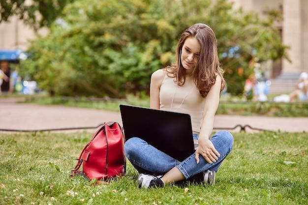 Student met laptop zit in het park op zomerdag
