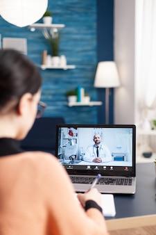Student met online videcall-conferentie met arts-arts die overleg pleegt over zorgbehandeling. geduldige vrouw die laptopcomputer gebruikt voor medisch consult terwijl ze in de woonkamer zit