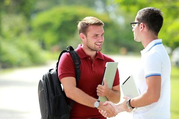 Student met rugzak blij zijn vriend te ontmoeten en vervolgens de hand te schudden