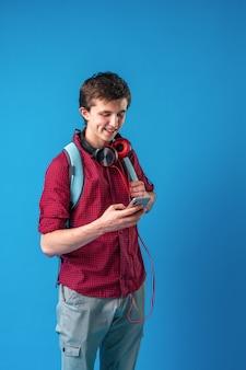 Student met rugzak, mobiele telefoon en koptelefoon communiceert via internet