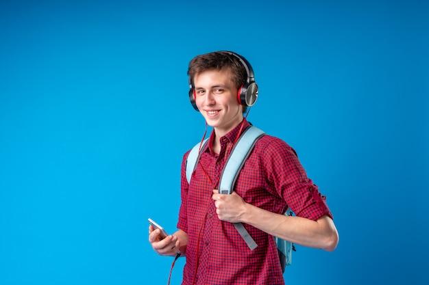 Student met rugzak, mobiele telefoon en koptelefoon luisteren naar muziek