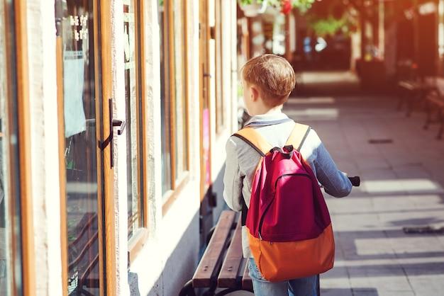 Student met rugzak op straat. terug naar schoolconcept. achteraanzicht van kind met scooter op straat. leerling met schooltas die na school naar huis gaat.