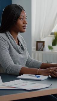 Student met zwarte huid die online cursussen doorbladert en schoolhuiswerk schrijft op de computer tijdens universitaire webinar