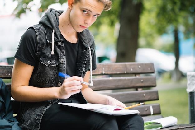 Student op bank met notitieblokken
