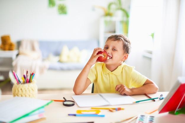 Student op een pauze met plezier een rode appel eten.
