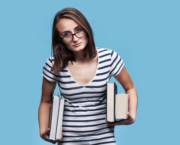 Student op witte muur met boeken