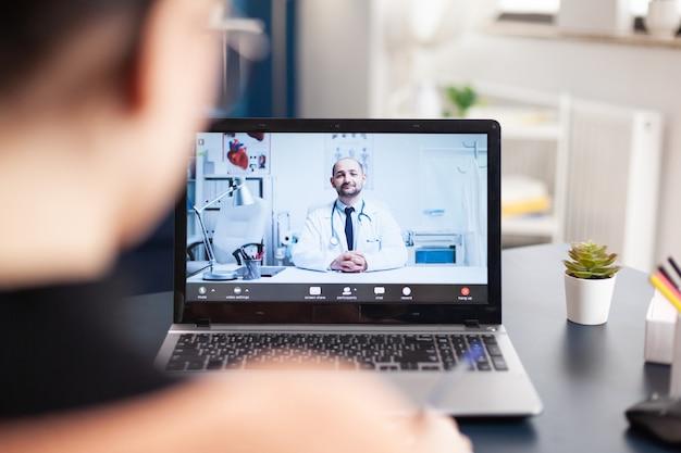 Student patiënt consulterende therapeut arts met online videocall consult tijdens coronavirus quarantaine. jonge vrouw praat over medische behandeling tegen ziekte terwijl ze in de woonkamer zit