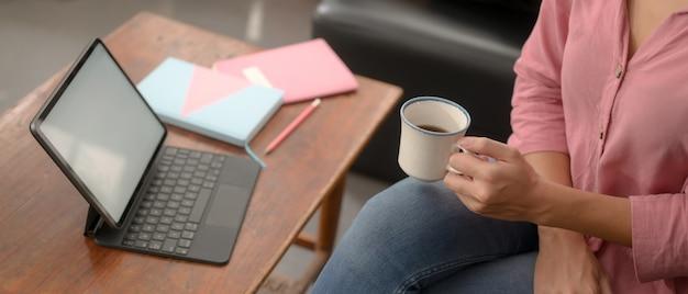 Student pauze met koffie terwijl online studeren met mock-up tablet in de woonkamer