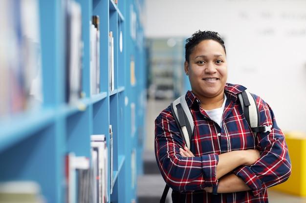 Student poseren in bibliotheek