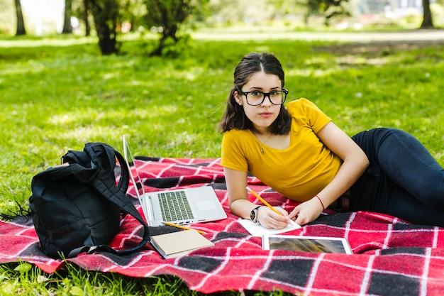 Student poseren met een bril op het gras
