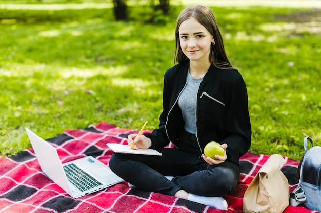 Student poseren met notitieboekje en appel
