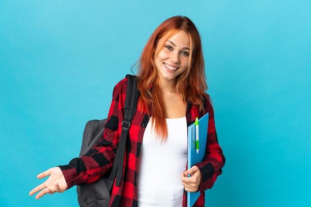 Student russische vrouw geïsoleerd op blauw blij en lachend