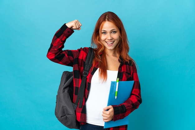 Student russische vrouw geïsoleerd op blauw doet sterk gebaar