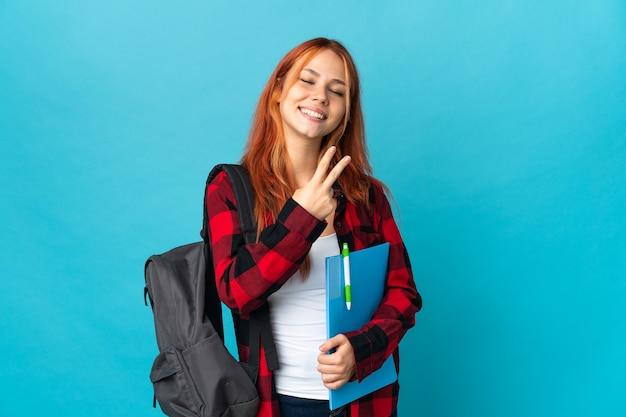 Student russische vrouw geïsoleerd op blauw glimlachend en overwinning teken tonen
