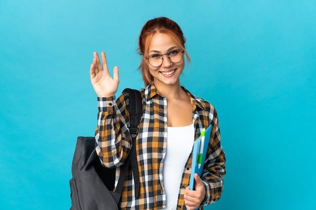 Student russische vrouw geïsoleerd op blauw groeten met hand met gelukkige uitdrukking