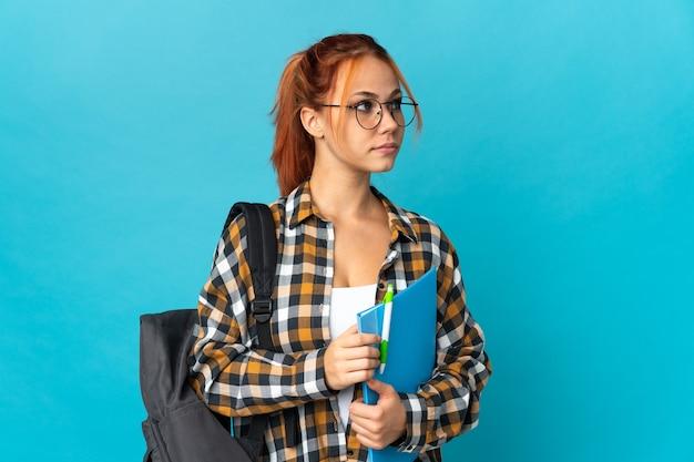 Student russische vrouw geïsoleerd op blauw met de armen gekruist