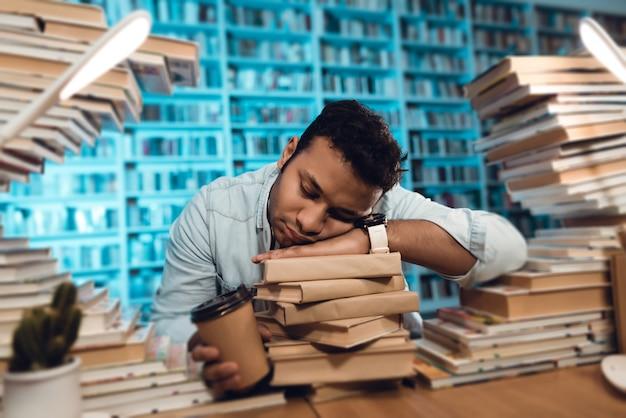 Student slaapt in de bibliotheek 's nachts