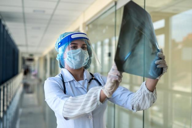 Student-stagiair in een beschermend pak en gezichtsbescherming kijkt naar een röntgenfilm