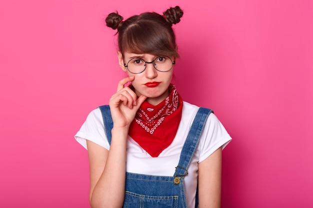 Student status geïsoleerd over roze in studio, wat betreft haar gezicht met vingers