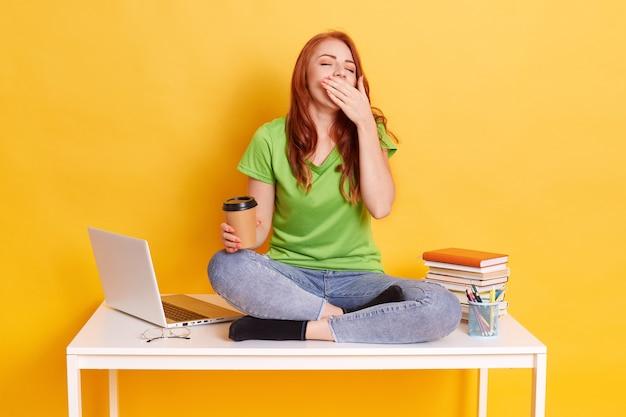 Student studeert of bereidt zich voor op examens, moe en slaperig zijn, op tafel zitten met gekruiste benen en geeuwen, spijkerbroek en groen t-shirt dragen dat over gele achtergrond wordt geïsoleerd.