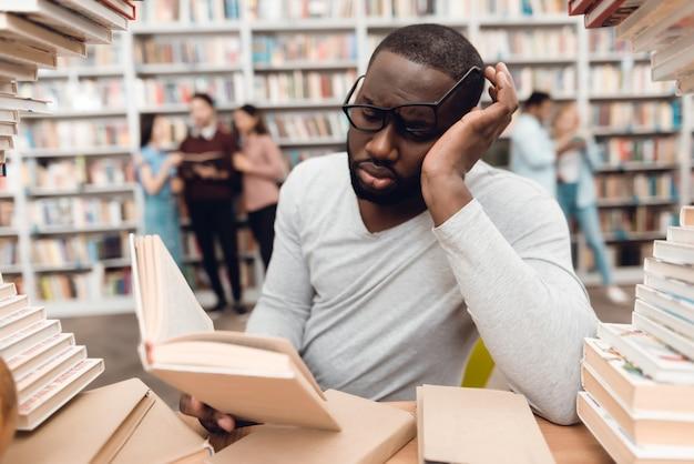Student studeert verveeld en moe in de bibliotheek.
