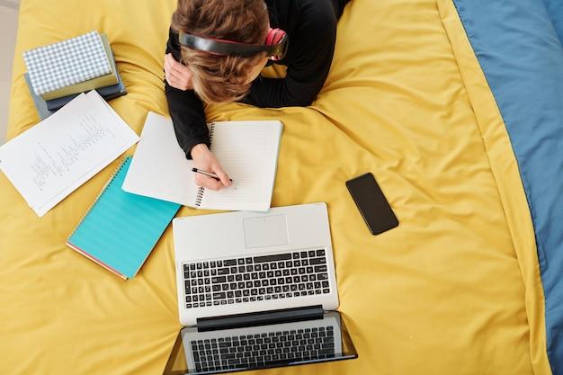 Student tekenen en schrijven in schrift bij het nadenken over een computerprogramma of schoolproject