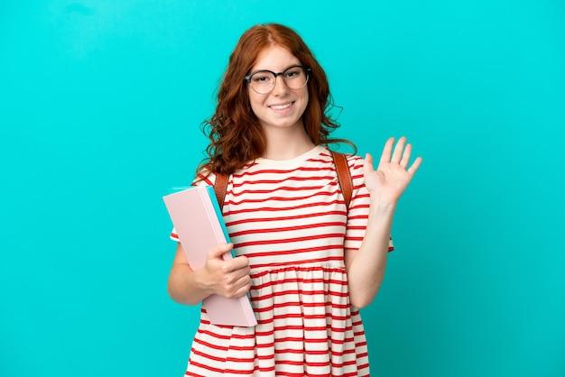 Student tiener roodharige meisje geïsoleerd op blauwe achtergrond saluerend met de hand met gelukkige expressie