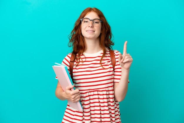 Student tiener roodharige meisje geïsoleerd op blauwe achtergrond tonen en optillen van een vinger in teken van de best