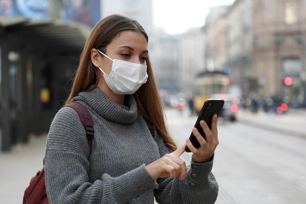 Student tienermeisje met beschermend masker betalen voor online transportkaartje